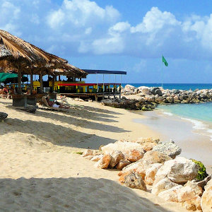 Colorful beach bar, straw huts white sandy beach location in St. Martin