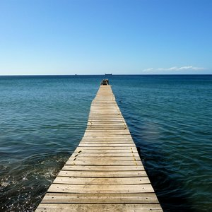 Wooden jetty over dark blue sea with infinity view on location in Dominica
