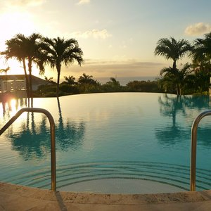 Infinity pool in tropical resort facing Caribbean sunset